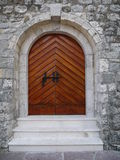 Wooden arch doors at medieval castle in Budva.  Royalty Free Stock Images