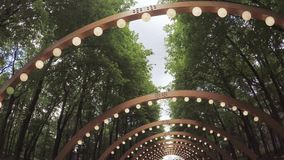 Wooden arch with lanterns. In city park passage under wooden arch with lanterns stock video footage