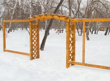 Wooden arch with grating in the Park in winter, cloudy day and snow. Wooden arch in the Park in winter, cloudy day and snow Stock Photos