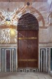 Wooden arched door on stone wall decorated with marble panels and lantern shadows on the wall, Old Cairo, Egypt stock photos