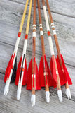 Wooden archery arrows. Wooden archery homemade arrows with plastic nocks and natural feathers , vertical Royalty Free Stock Photography