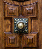 Wooden architectonic decoration. Architectonic decoration. This is a wooden decorated part of a door with a golden doorknob Stock Photo
