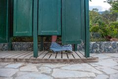 A wooden architecture painted with dark green. The half way door room sitting above the tiled pathway. A man underpants falling do royalty free stock photos