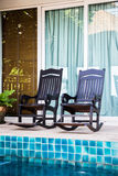 Wooden arm chairs beside the pool Royalty Free Stock Photo