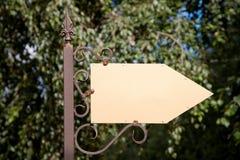 Wooden arrow cursor on a metal pole Stock Photos