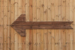 A wooden arrow on the wooden wall Royalty Free Stock Image