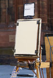 Wooden art easel tool for drawing. Old and used wooden art easel tool for drawing standing outside on a marketplace in france stock photo