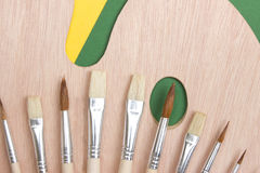 Wooden art palette with a brush Royalty Free Stock Images
