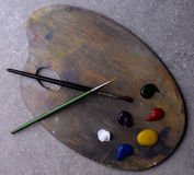Wooden art palette with colors and two brushes Royalty Free Stock Image