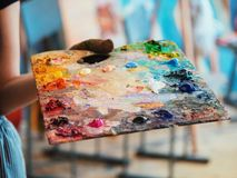 Wooden art palette with oil paints. Mixing colors together. Artistic instrument with many colors. Working tool with stock photos