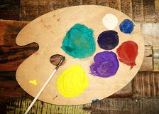 Wooden art palette with paint and brush on vintage background Royalty Free Stock Photos