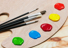 Wooden art palette with paints and brushes Stock Photography