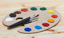 Wooden art palette with paints and brushes Royalty Free Stock Photos
