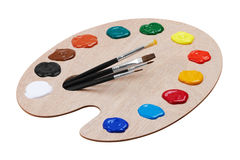 Wooden art palette with paints and brushes Stock Photos