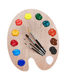 Wooden art palette with paints and brushes Royalty Free Stock Photography
