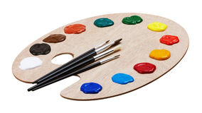 Wooden art palette with paints and brushes Royalty Free Stock Images