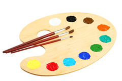 Wooden art palette with paints isolated on a white Royalty Free Stock Photo