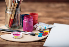 Wooden art palette with tubes of oil paints and a brush. Art and craft tools. Artist`s brush, canvas, palette knife. Space for tex. T. Items for children`s royalty free stock photography