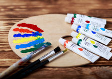 Wooden art palette with tubes of oil paints and a brush. Art and craft tools. Artist`s brush, canvas, palette knife. Space for tex. T. Items for children`s stock photos