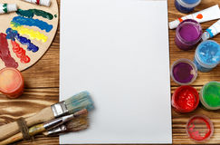 Wooden art palette with tubes of oil paints and a brush. Art and craft tools. Artist`s brush, canvas, palette knife. Space for tex. T. Items for children`s royalty free stock photo