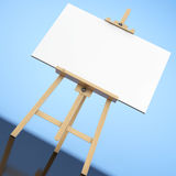Wooden Artist Easel with White Mock Up Canvas. 3d Rendering. Wooden Artist Easel with White Mock Up Canvas on a blue background. 3d Rendering Stock Photo