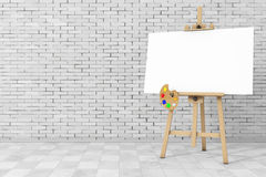Wooden Artist Easel with White Mock Up Canvas and Palette. 3d Re. Wooden Artist Easel with White Mock Up Canvas and Palette in front of brick wall. 3d Rendering Royalty Free Stock Photo