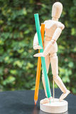 Wooden artist manikin standing with colour pencil Stock Images
