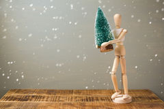 Wooden artistic figure holding christmas tree. Christmas holiday concept Royalty Free Stock Images