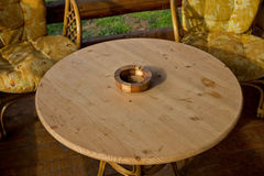 Wooden ashtray at a round wooden table 02. Wooden ashtray at a round wooden table with bamboo chairs Stock Photo