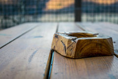 Wooden ashtray on a wooden table , closeup.  Royalty Free Stock Images