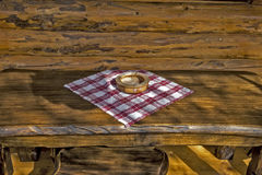 Wooden ashtray on a wooden table. On the cottages from logs balcony Stock Photography