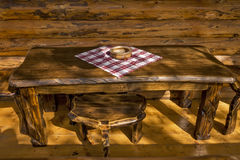 Wooden ashtray on a wooden table. On the cottages from logs balcony Royalty Free Stock Photo