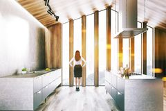 Wooden attic kitchen with island, woman stock photo
