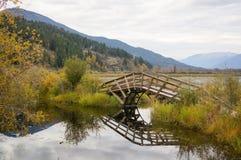 Wooden autumn bridge. Wooden bridge crosses lake with reflection and autumn colours. Creston, BC, Canada Royalty Free Stock Image
