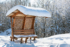 Wooden awning bench covered by snow Stock Photos