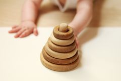 Wooden baby pyramid - representing pyramid of needs. Baby`s hands trying to reach the toy royalty free stock photos