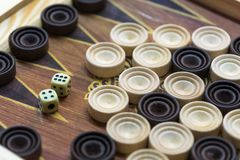 Wooden backgammon. Play a board game. The hand is throwing dice royalty free stock images