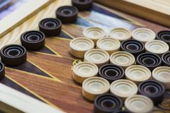 Wooden backgammon. Play a board game. The hand is throwing dice royalty free stock photography
