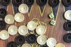 Wooden backgammon. Play a board game. The hand is throwing dice stock photo