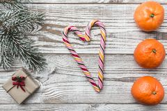 Wooden background. Albi. Fir branch green. Oranges. Gift. Heart of colored candies. Winter card. Space for Christmas or New Year. Stock Images