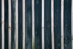 Wall of boards of dark color and light bars. A wooden background with alternating boards of dark color and light bars Stock Photos