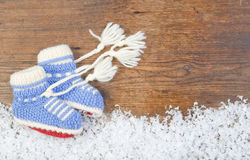 Wooden background with babys bootees and winter snow on the bor Stock Images