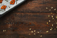 Wooden background with baked pumpkin flat lay. Top view on dark rustic kitchen table with prepared squash slices and seeds frame, free space for text Stock Photo