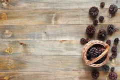 Wooden background with basket and pine cones royalty free stock image