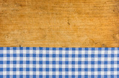 Wooden background with a blue checkered tablecloth Royalty Free Stock Photography