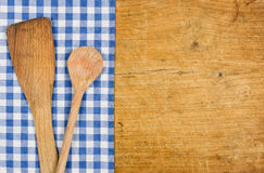 Wooden background with a blue checkered tablecloth and wooden spoon Stock Photography