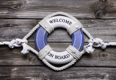 Wooden background with blue and white life preserver for maritim Stock Images