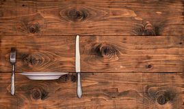 Wooden background from boards with kitchenware and a thrust rib plate. Wooden background from boards with a knife and fork on the edge of the installed plate Royalty Free Stock Photography