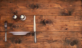 Wooden background from boards with kitchenware and a thrust rib plate. Wooden background from boards with knife, fork, pepper shaker, salt shaker, and on the Stock Images