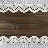 Wooden background with borders of embroidered lace